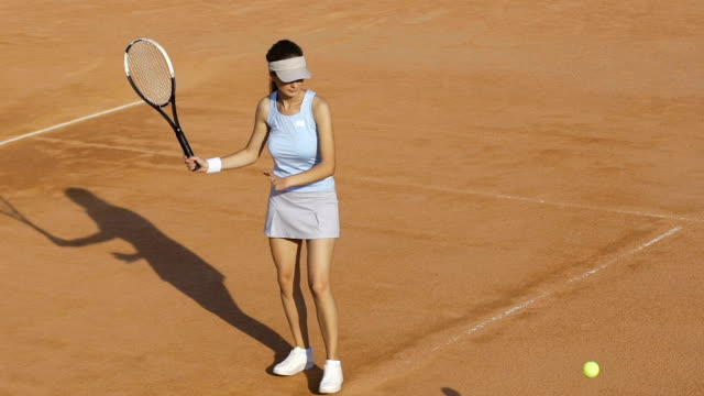 Fit woman in white sportswear receives ball during tennis tournament, slowmotion video