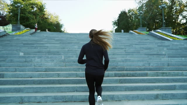 Fit woman jogging on staircase in city Woman with ponytail wearing black sportswear and white sneakers running upstairs in city park. Following shot of fit female jogging in the morning. Concept of fitness staircases stock videos & royalty-free footage