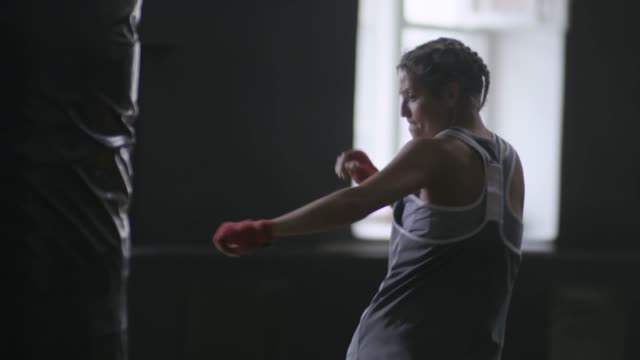 vídeos de stock e filmes b-roll de fit woman kicking punching bag - boxe tailandês