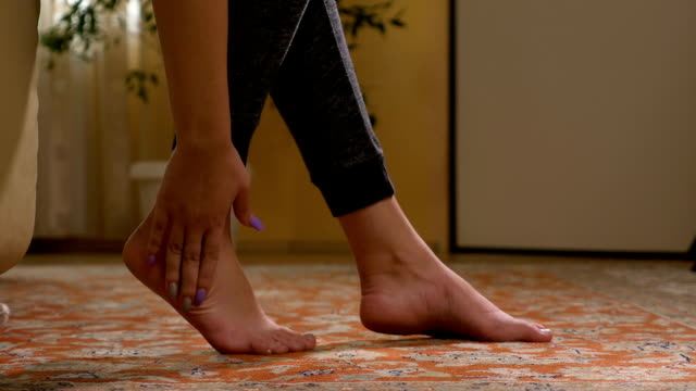 Fit woman massaging sore barefoot sole to relieve the pain and stress video