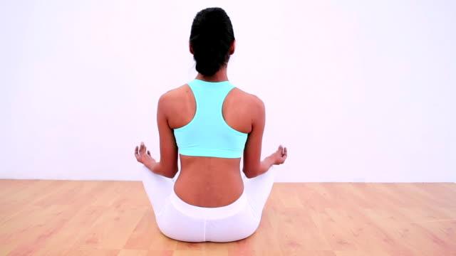 dopasowanie kobieta w pozycji lotosu medytować - biustonosz sportowy filmów i materiałów b-roll