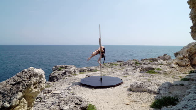 Fit woman performs acrobatic pole dance tricks on pole above the sea Fit woman performs acrobatic pole dance tricks on pole during extreme outdoor fitness exercise on a cliff above the sea leotard stock videos & royalty-free footage