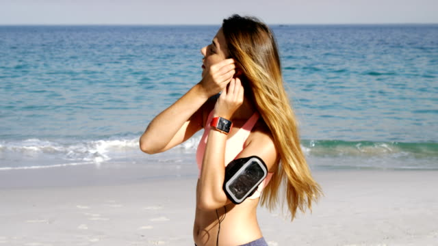 Fit woman putting earphones in her ear before jogging video