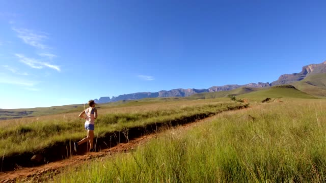 fit kvinna som springer längs en bergs stig - jogging hill bildbanksvideor och videomaterial från bakom kulisserna