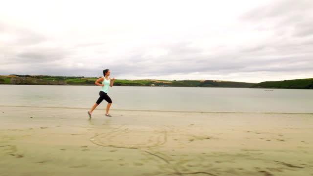 силуэт женщина, бег на песчаном пляже - спортивный бюстгальтер стоковые видео и кадры b-roll