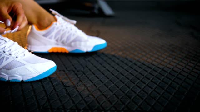 スニーカーの靴ひもを結ぶ体育館の床に座っている女性に合います。 - 女性選手点の映像素材/bロール