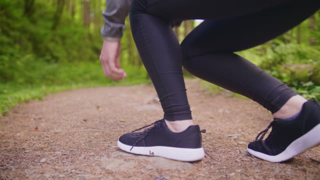 Fit Woman Tying Shoelace And Jogging At Forest Trail Lockdown shot of fit woman tying shoelace before jogging. Surface level shot of female athlete running on forest trail. She is representing healthy lifestyle. 4K Resolution. lockdown viewpoint stock videos & royalty-free footage