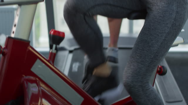 Fit Woman Using Exercise Machine Tilt up medium shot of determined young tattooed woman working out on exercise bike while training in gym exercise bike stock videos & royalty-free footage