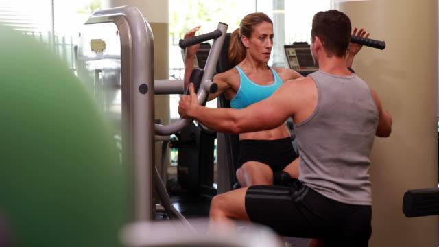 силуэт женщина, используя гантели machine за руки с ее тренером - спортивный бюстгальтер стоковые видео и кадры b-roll