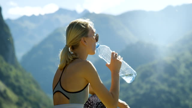 Fit Young Blonde Woman in Sportswear Sits on the Mountain and Drinks Water while Resting. Breathtaking Hills, Mountains, and Valley View. Summer Time with Scenic Nature View. video