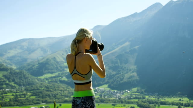 Fit Young Blonde Woman in Sportswear Takes Professional Photos with Her DSLR Camera. She Photographs Breathtaking Hills, Mountains, and Valley. Summer Time with Scenic Nature View. video
