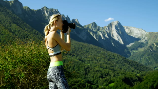 Fit Young Blonde Woman in Sportswear Takes Professional Pictures with Her DSLR Camera. She Photographs Breathtaking Hills, Mountains, and Valley. Summer Time with Scenic Nature View. video