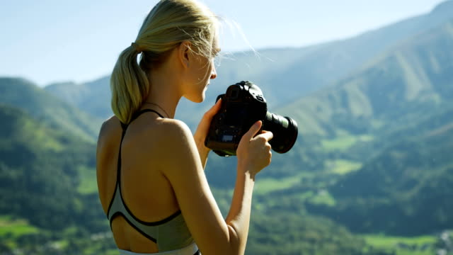 Fit Young Blonde Woman in Sportswear Takes Professional Pictures with Her DSLR Camera. She Photographs Breathtaking Hills, Mountains and Valley. Summer Time with Scenic Nature View. video
