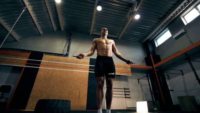 Fit young man doing jump rope exercises at gym video