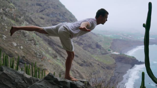 fit young man practices sun salutation yoga in mountain for ocean. young man enjoying meditation and yoga. fitness, sport, people and lifestyle concept - young man making yoga exercises - armonia video stock e b–roll