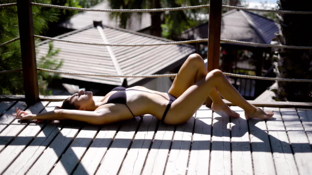 Fit young woman in bikini sunbathing on balcony of hotel video