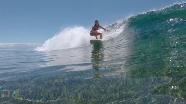 vídeos de stock e filmes b-roll de underwater: fit young woman on summer holiday surfs a crystal clear barrel wave. - desportista
