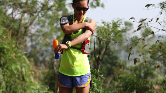 fitness asian woman trail runner applying sunscreen scream lotion before cross country running on forest mountain - sun cream stock videos & royalty-free footage