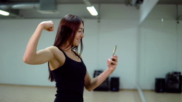 stockvideo's en b-roll-footage met fitness concept. jonge vrouw in de sport uniforme doen selfie in een sporthal. - bewondering