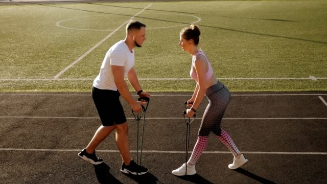 A fitness couple trains at the stadium in the summer with an elastic expander.