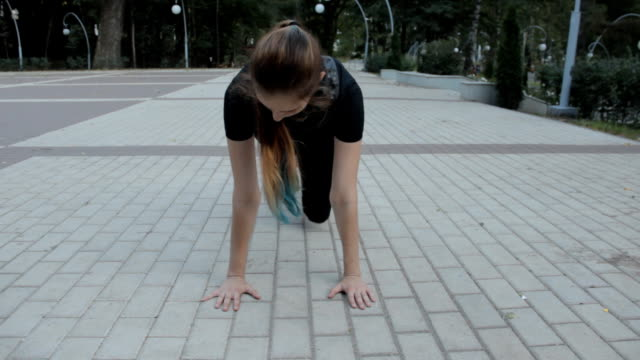 A fitness fan dressed in black apparel. doing pushups in a park with her hands rested on the ground A fitness fan dressed in black apparel. doing pushups in a park with her hands rested on the ground. Front view. bodyweight training stock videos & royalty-free footage