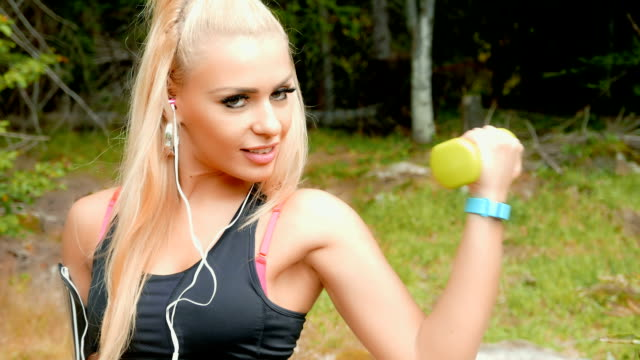Fitness girl exercising with dumbbells outdoors and looking at camera video