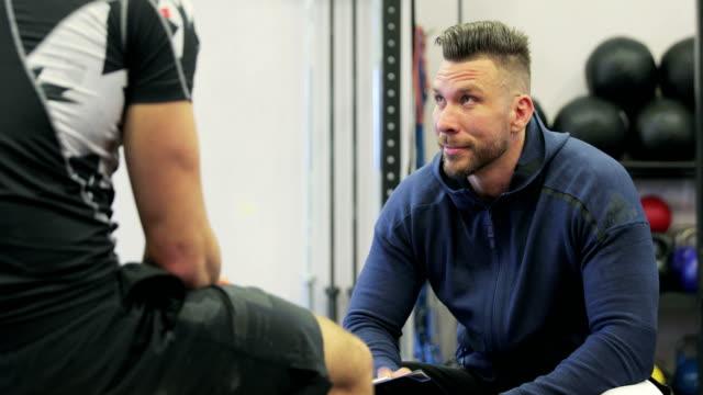 vídeos y material grabado en eventos de stock de instructor de fitness y amigos teniendo una discusión después de entrenamiento - entrenador personal