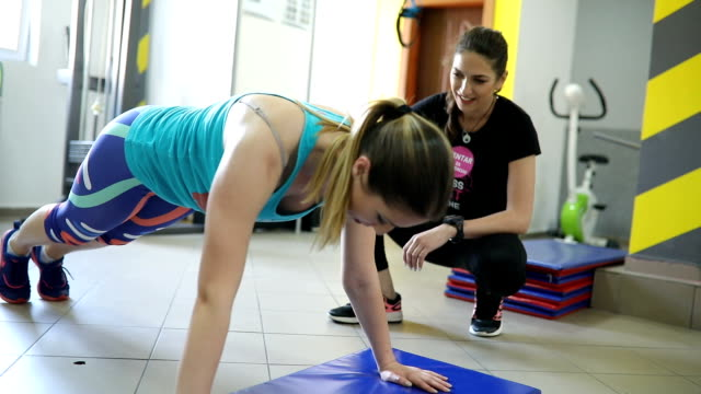 Fitness instructor exercising with a client video