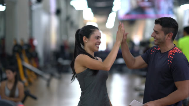 Fitness instructor giving a high five to his customer video