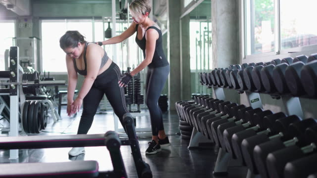 fitness instructor helps young woman with exercise - otyły filmów i materiałów b-roll