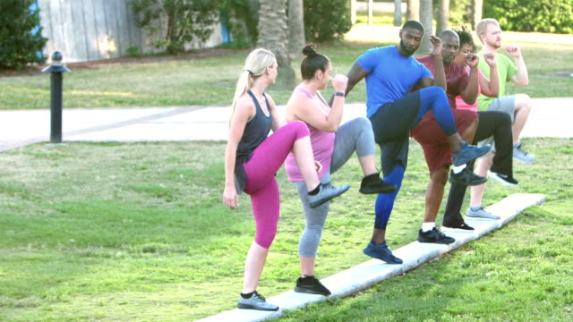 Fitness instructor leading multi-ethnic exercise class video