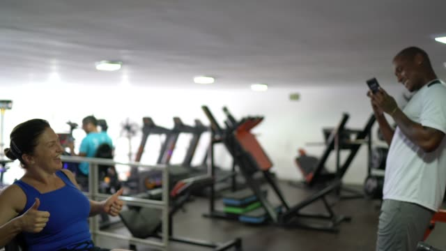 Fitness instructor taking photos of a mature woman at gym