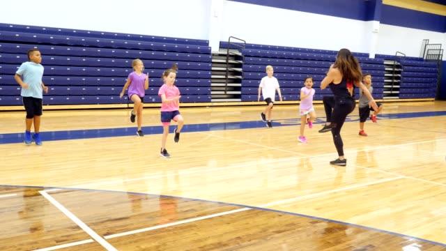vídeos y material grabado en eventos de stock de instructor de fitness enseña clase de cardio para niños - gimnasia
