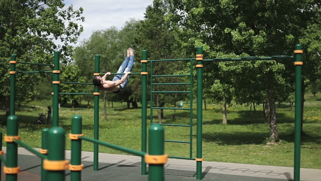Fitness man doing flips on the bar in the park. video