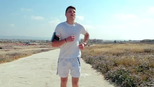 Fitness man in headphones on a run. Man jogging on road in summer day Man running along road in summer. Fitness man in headphones on a run. Man runner looking at timer. Running man close up. Men jogging. gym training at summer. Healthy lifestyle human back stock videos & royalty-free footage