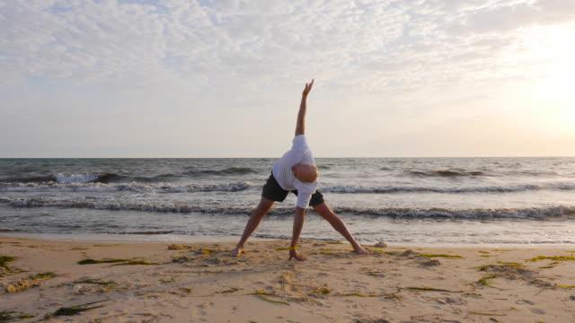 fitness man practising yoga asana while morning training on sea beach - posizione corretta video stock e b–roll