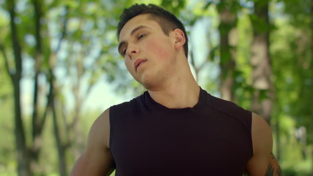 Fitness man warm up neck outdoor. Closeup of fit man stretching in park video