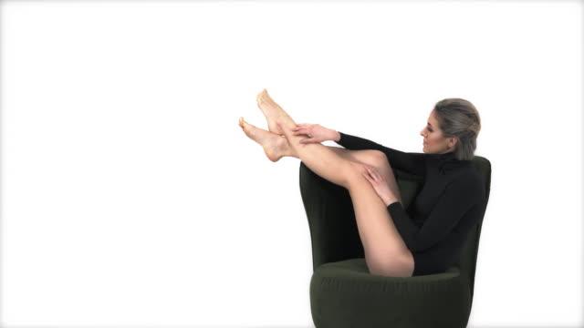 fitness modell i svarta sportkläder trikåer avkopplande på fåtölj och röra hennes ben försiktigt. mode- och sportkoncept - gympingdräkt bildbanksvideor och videomaterial från bakom kulisserna