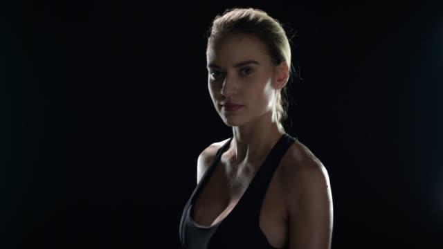fitness modell poserar med handduk på svart bakgrund. idrotts kvinna med handduk - black woman towel workout bildbanksvideor och videomaterial från bakom kulisserna