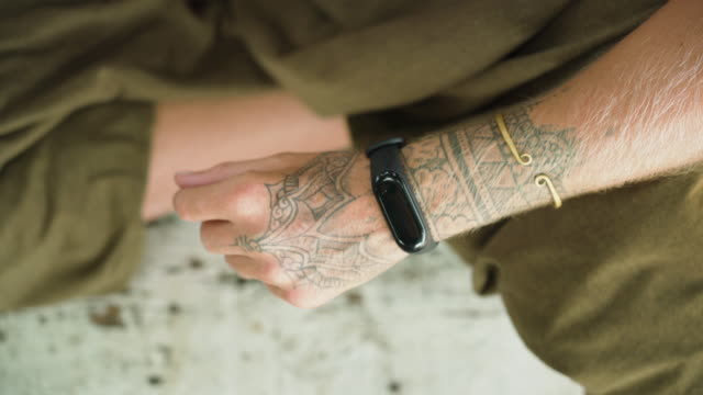 Fitness tracker watch on tattoed female wrist above view