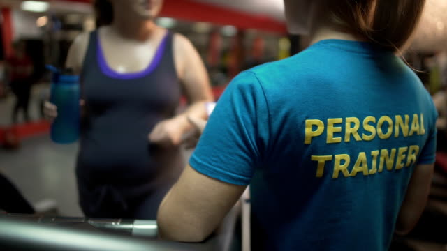 Fitness trainer consulting overweight lady exercising in gym, weightloss control video