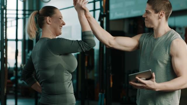 vídeos de stock, filmes e b-roll de instrutor de fitness no ginásio, falando com o cliente sobre resultados e celebrando com cinco - personal trainer