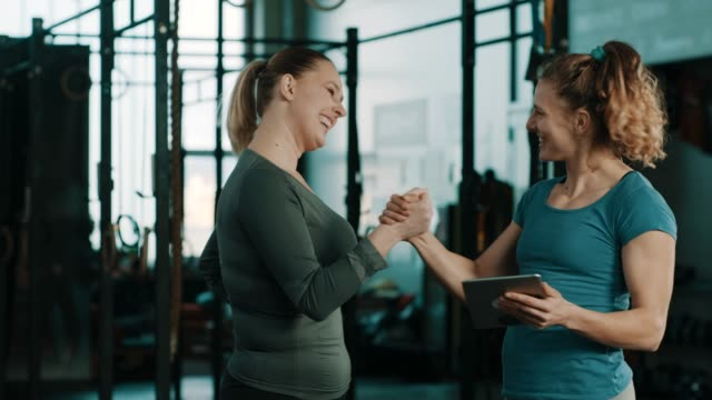 fitness trainer in gym talking to client about results and celebrating with high five - kurs ćwiczeń filmów i materiałów b-roll