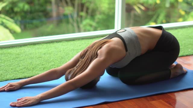 fitness kvinna gör yoga hemma - ligga på mage bildbanksvideor och videomaterial från bakom kulisserna