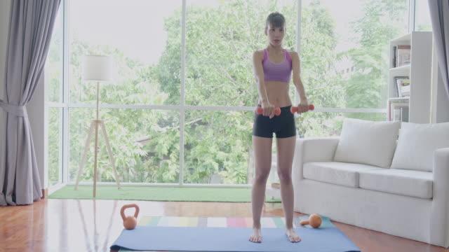 fitness donna excerise, braccia, manubri, excerise, in piedi. bella donna asiatica nello sport. - arto umano video stock e b–roll