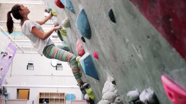 Fitness Woman on Climbing Wall A woman climbing on a vertical wall indoors, learning to use all her muscles to get to the top. hobbies stock videos & royalty-free footage