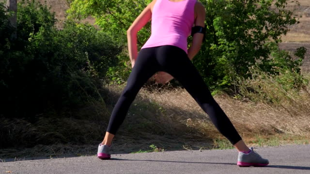 Fitness woman runner stretching before run on the road video
