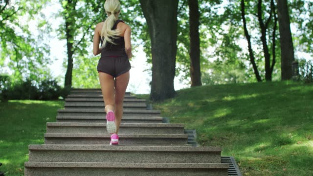 Fitness woman running up stairs while morning jogging at summer park