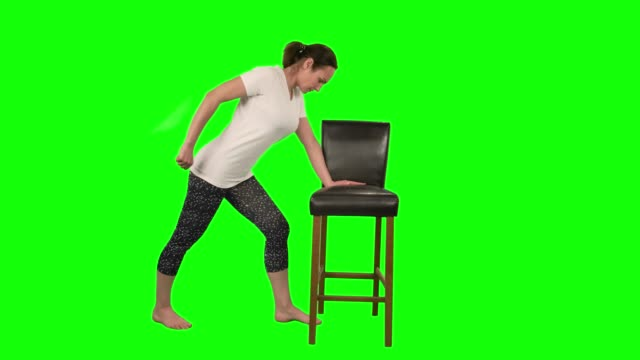 vídeos de stock e filmes b-roll de fitness woman standing in pose leaning on black chair and doing exercises for rehabilitation shoulder isolated at green screen in studio - teeshirt template