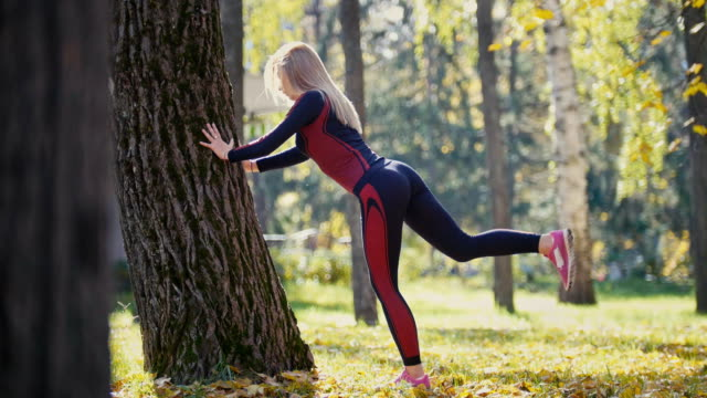 Fitness woman strength training doing workout at sunny autumn park. Fit caucasian sporty girl exercising her body near tree - lifts legs alternately video